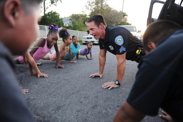 police officer doing push ups with children