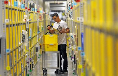 man picking product at amazon warehouse